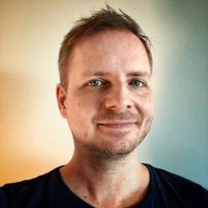Portraitfoto von Shenja Jeworek, heller Hauttyp, Dreitage-Bart, blaue Augen und eine etwas durchgewuschelte Kurzhaarfrisur.